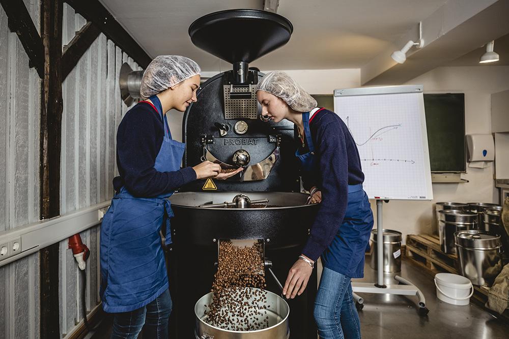 Die Schülerinnen und Schüler rösten die Kaffeebohnen und prüfen deren Qualität.