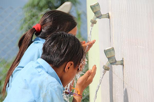 Zwei Schulkinder in Nepal trinken sauberes Trinkwasser aus einem Wasserhahn. Das Kinderhilfswerk Eine Welt hat den Bau des Schulgebäudes unterstützt.