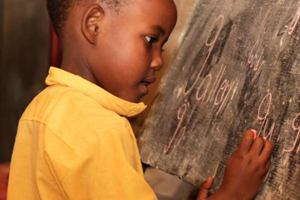 Ein Schulkind in Mali schreibt mit Kreide auf einer Tafel. Seit 1995 hat das Kinderhilfswerk Eine Welt über 20 Schulen in Mali gebaut.