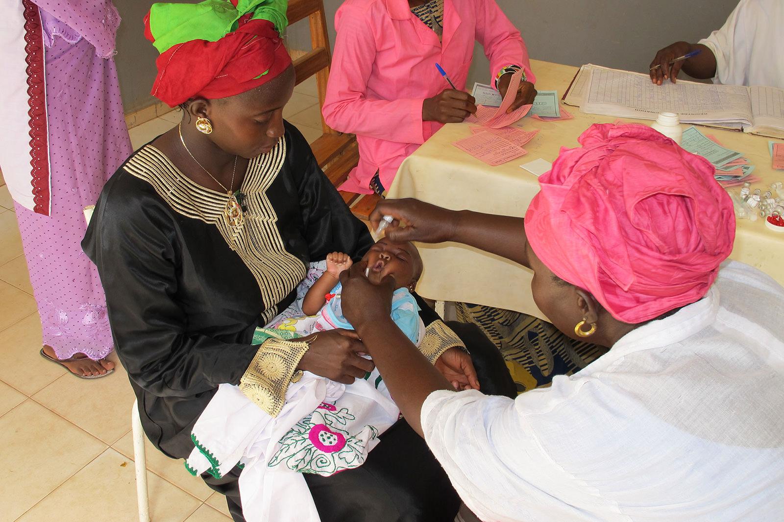 Eine malische Mutter sitzt mit ihrem Kind bei einer Ärztin. Dort erhält das Kind eine Schluckimpfung.
