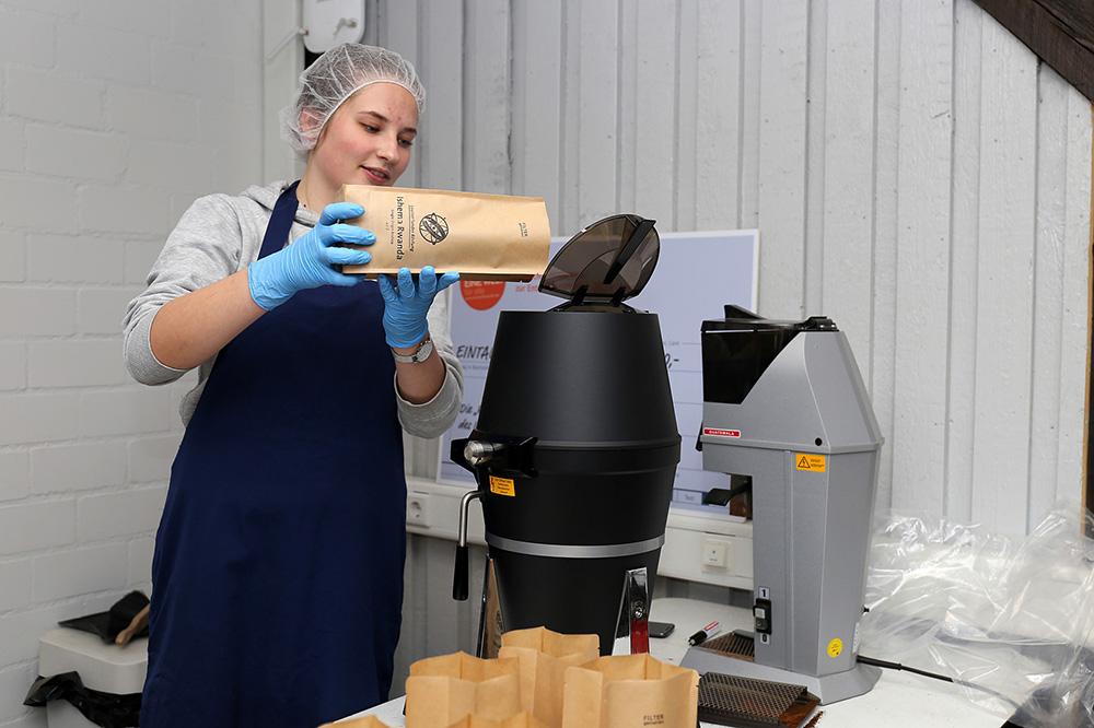 Eine Schülerin befüllt die Kaffeemühle mit den Bohnen.