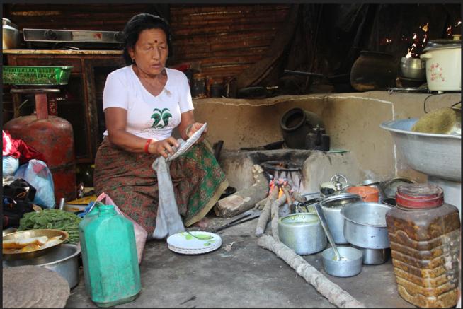 Eine Nepalesin wäscht das Geschirr nach dem Essen in der Schule ab.