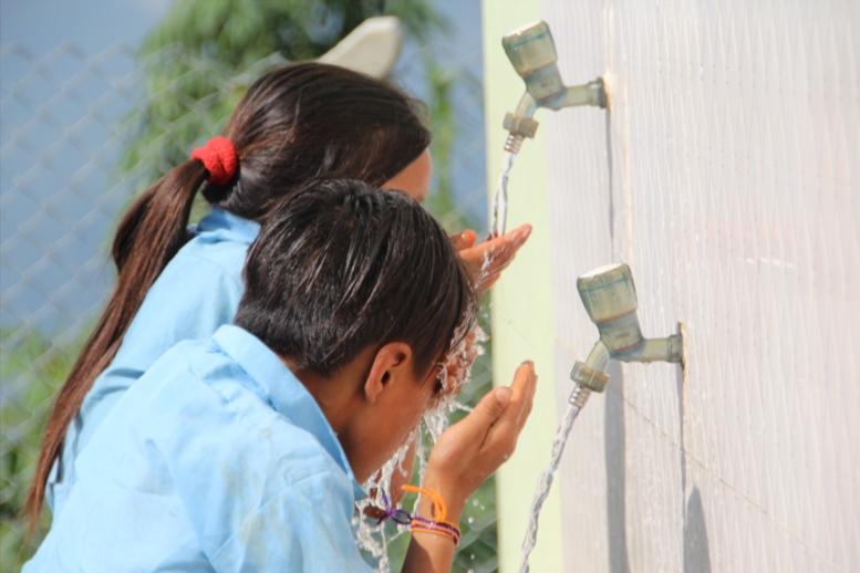 Die Kinder erfrischen sich am neuen Trinkwasserzugang in einer Grundschule in Purlung/ Nepal.