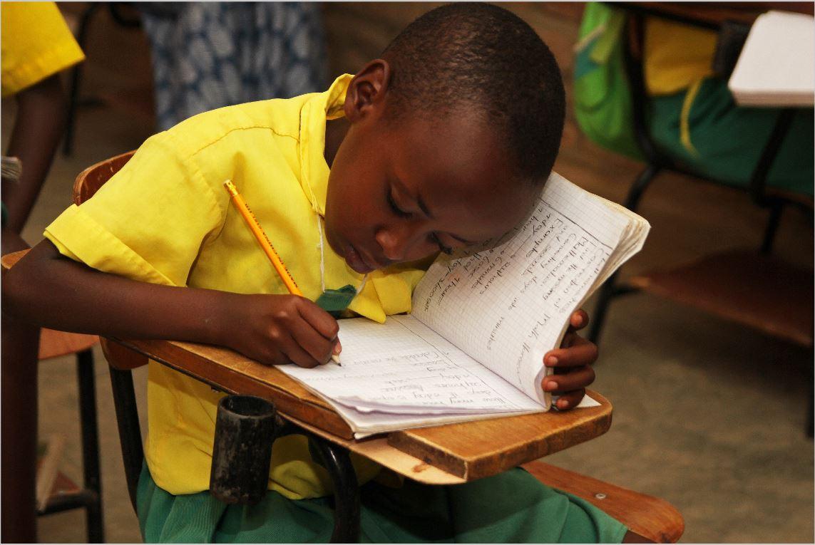 Ein Schüler aus Ruanda schreibt in sein Schulheft.