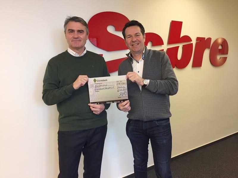 Uwe Schmidt, Vorstand des Kinderhilfswerks Eine Welt, nimmt eine Spende von dem Unternehmen Sabre entgegen.