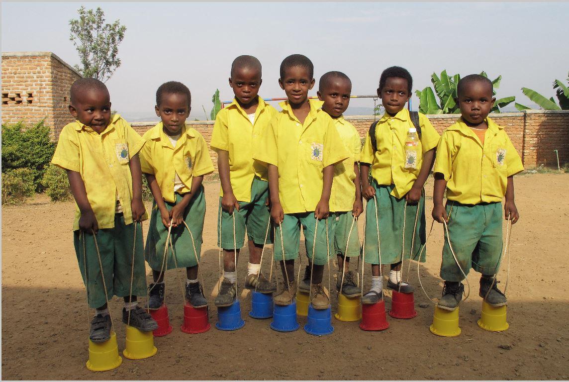 Schüler spielen mit Stelzeneimern. Seit Anfang 2013 unterstützt das Kinderhilfswerk Eine Welt die Menschen in Ntarama in Ruandas Zentralprovinz durch die Errichtung und den Unterhalt der Vor- und Primarschule »Les Genies«.